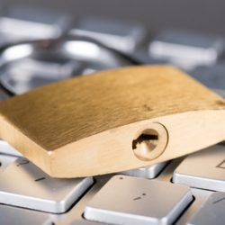 Padlock on computer keyboard, closeup